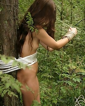 Hot teen babe enjoys some provocative rope play tied up to a tree in the forest